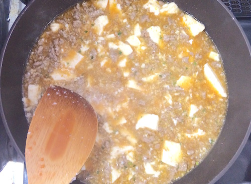 素と豆腐を加えて麻婆豆腐を作る