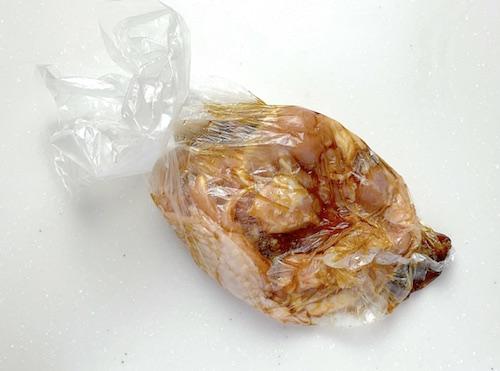 鶏もも肉に調味料をもみこむ